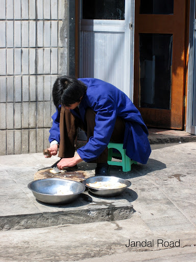 Preparing a meal on the ground, next to traffic.