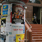 An old fashioned poster pillar, in the back Nadia and Agnieszka entering SDK.