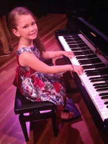 Girl sits at grand piano