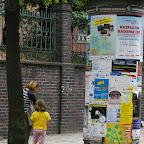 An old fashioned poster pillar in front of the church.