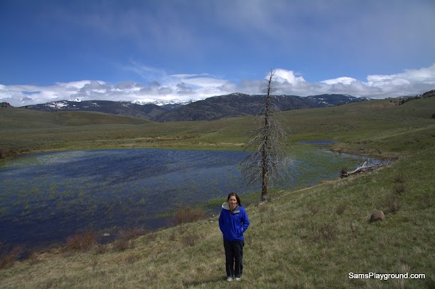 Yellowstone with Renee infront of the pond with the light striking the clouds above the mountains in the distance