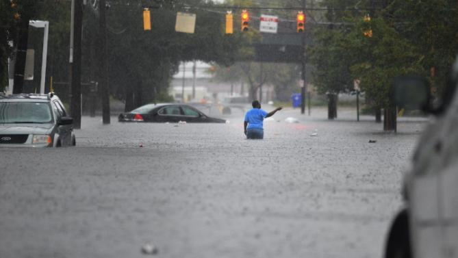 Flooding from heavy rain swamps the intersection of Huger Street and King Street in Charleston, S.C. on Saturday,  Oct 3, 2015.  The National Weather Service says the risk of flooding will continue through Monday morning, especially in parts of North and South Carolina that already have gotten up to 11 inches of rain this week. Forecasters say some areas could see storm totals as high as 15 inches. (Matthew Fortner/The Post And Courier via AP)