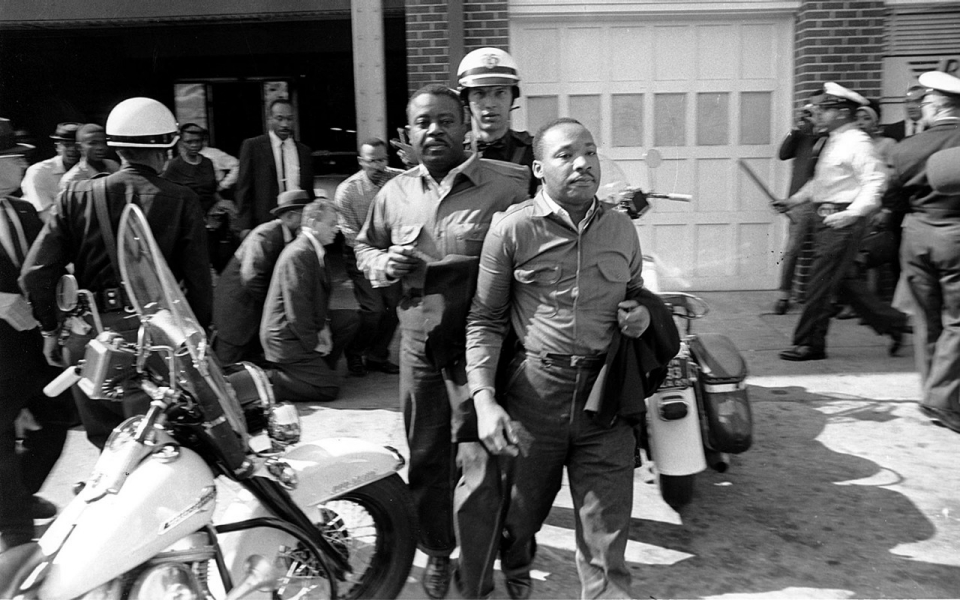 El pastor Ralph Abernathy, left, y el pastor Martin Luther King Jr., son arrestados por la policías después de conducir a  manifestantes en la sección comercial de Birmingham, Ala.,el 12 de abril de  1963.
