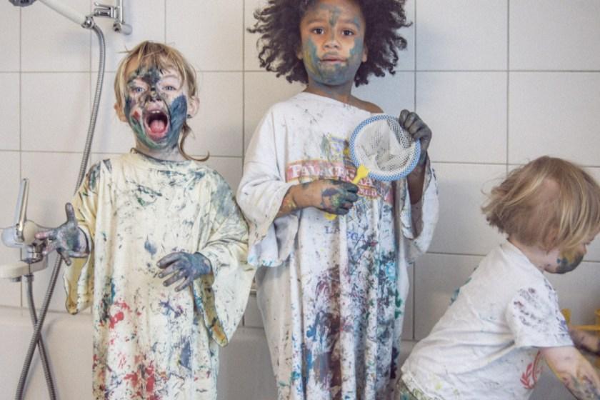 Malen mit Fingerfarbe. Die drei Mädels voll mit Fingerfarbe in der Badewanne.