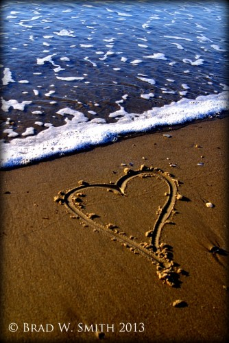 heart drawn in the sand near ocean waves