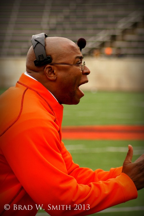 bald black man in orange jacket, headphones, at edge of football field