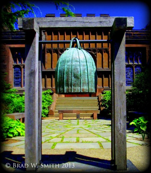 verdigris copper Asian bell hanging from wood stanchion on a flagstone plaza