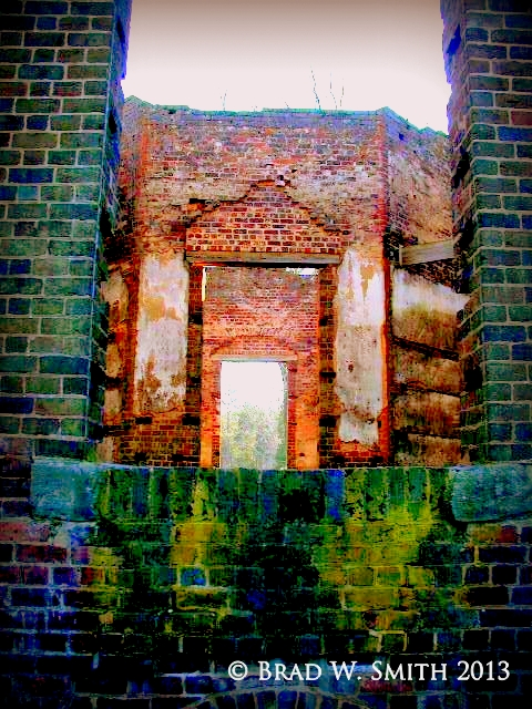 two crumbling brick pillars and porch foundation of what was a fine home; brick fireplace