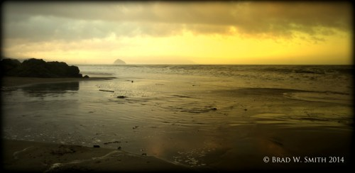 yellow sky above the ocean, dark clouds overhead, Morro Bay rock left