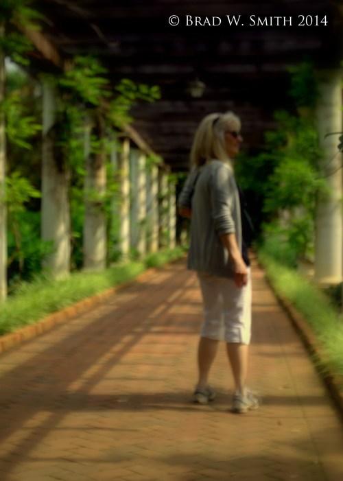 slender white woman, white crops, long white hair, sunny day, green vines and grasses around white pillard arbor, brick walkway