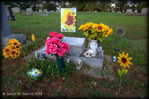 bouquets of sunflowers, pink roses, statue of jumping dolphin, basket of pastel-colored eggs surround headstone in cemetery