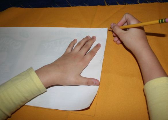 Picture shows a person holding a pattern down on a piece of fabric and penciling around it.