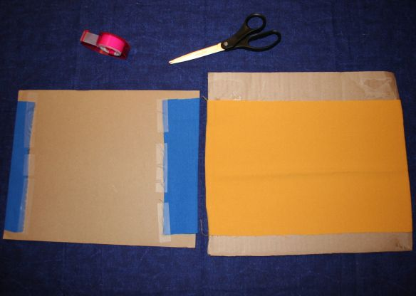The picture shows fabric taped to a piece of cardboard ready for painting.