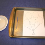 Shows a shallow baking tray with a sheet of card stock with a printed pattern on it. There is a paint brush and a small plate with some glue on it as well.