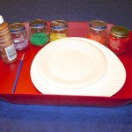 Shows a tray with 5 jars of colored sand, a paint brush, a bottle of glue, a small plate with glue on it, and a larger paper plate.