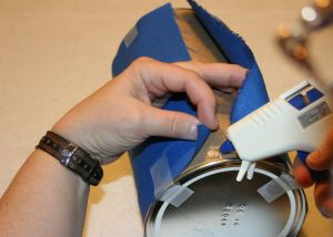 Image shows an adult hot gluing blue fabric to a container using tape to hold the fabric in place.