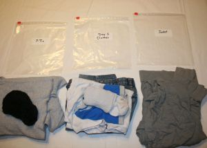 Image shows piles of folded clothes laid out next to labeled plastic bags for Scouting and Special Needs Children.
