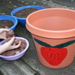 Image shows child picking up small rocks to put in a pot.