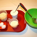 Image shows a red tray with mozzarella cheese, ricotta cheese, parmesan cheese and two eggs on it next to a green bowl with a large spoon in it.