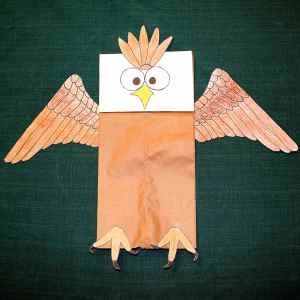 Image shows a paper bag decorated with an eagle's face, wings and feet to make a Veteran's Day craft.