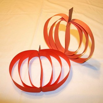 Image shows two large pumpkins made out of strips of construction paper.