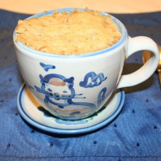 Image shows a coffee cup with a refrigerator microwave muffin cooked in it.
