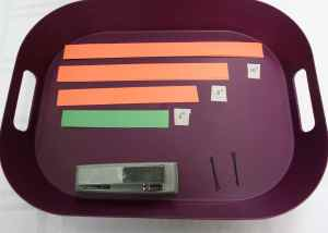 Image shows a purple tray with long strips of construction paper labeled by length, two bobby pins, and a stapler.