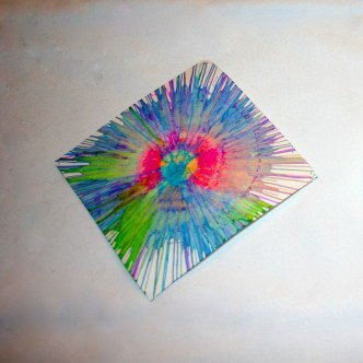 Image shows a diamond-shaped white paper with spin art colors on it.