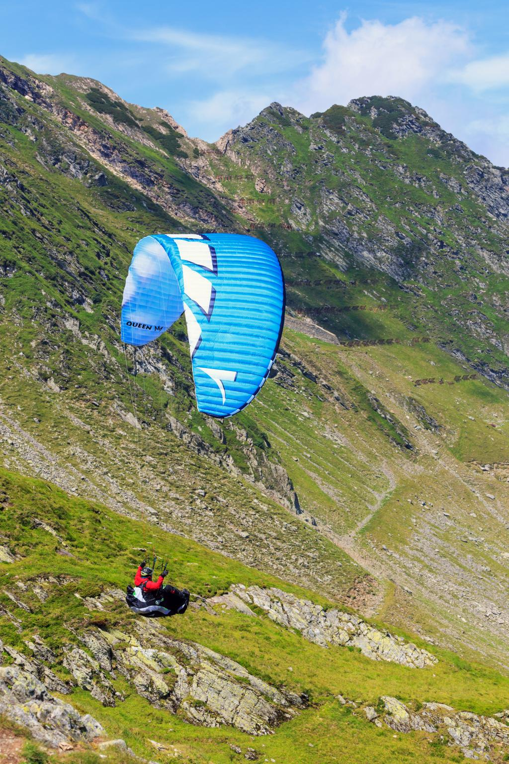 Balea Lake, Romania - JULY 21, 2014: Unidentified paraglider in Balea Lake, Fagaras Mountain, Romania. Paragliding is one of the most popular adventure sports in the world