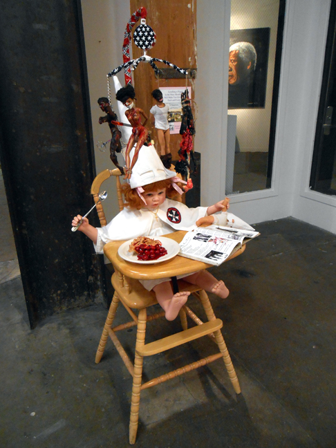 Lili Bernard. As American as Cherry Pie, 2014. Baby doll parts, Barbies, highchair, baby mobile, nails, cotton fabric, rope, chain, scissors, digital photos, children's book, acrylic paint, 24″x28″x52″ Available for purchase