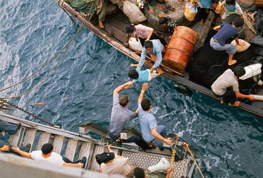 Crewmen of the amphibious cargo ship U.S.S. Durham (LKA-114) take Vietnamese refugees aboard from a small craft. The refugees will be transferred later by mechanized landing craft (LCM) to the freighter Transcolorado.