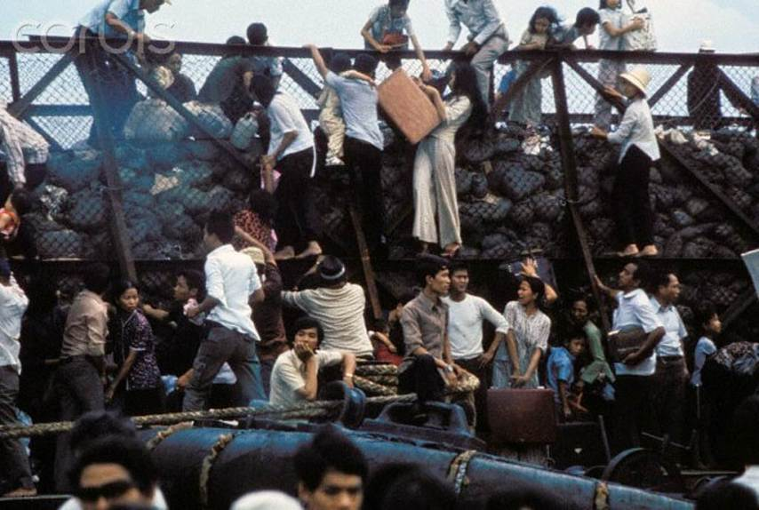 South Vietnamese clamber aboard barges in the port of Saigon in an attempt to escape from advancing North Vietnamese troops on the day of the Fall of Saigon that ended the Vietnam War --- Image by © Nik Wheeler/Corbis