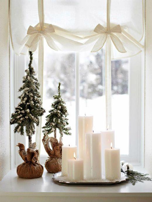 mini juletrær og lys i vindu