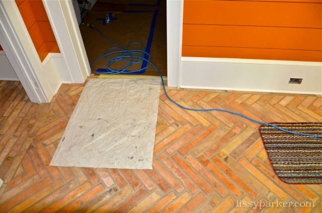 Antique French tiles are on the entry floor ...  the orange walls complement them