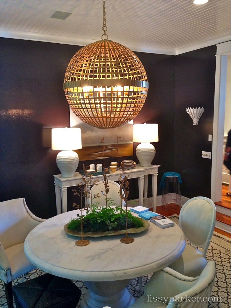 Dinning room features dark brown walls and round table and chandelier