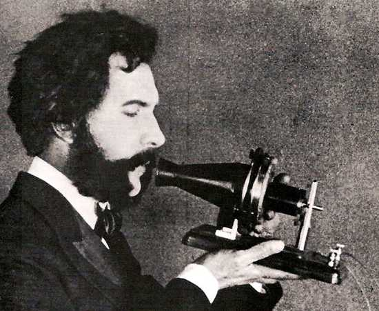 Alexander-Graham-Bell-Speaking-Into-Early-Telephone-1876