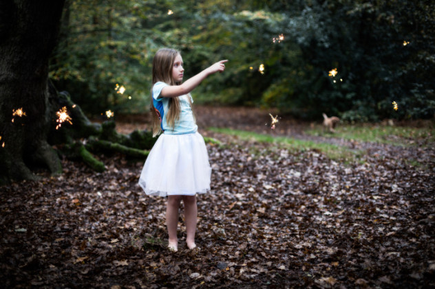 Young Girl in the Forest Pointing at Fairy Sparkles