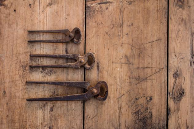Three vintage pliers on grunge wooden table