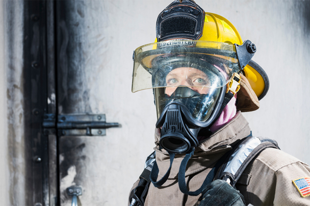 Female firefighter in protective gear and oxygen mask