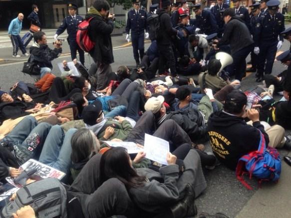 しばき隊、抗議のため路上にシットイン 警察に「建設的な行動をしなさい」と注意される