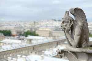 Bored Gargoyle knows how to kill time at Notre Dame de Paris