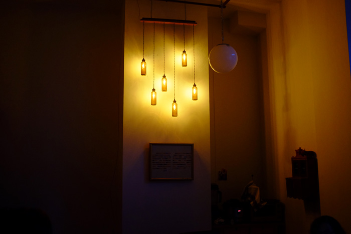 The chandelier hangs from two chains about two inches off the wall.