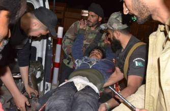 Pakistani volunteers and police officers rush an injured person to a hospital in Quetta Picture Courtesy: AP/Arshad Butt