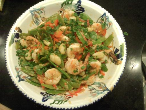 Gnocchi with shrimp and snow peas in a white bowl.