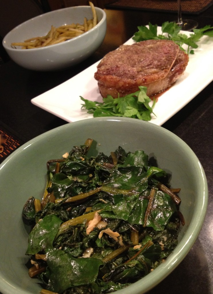 Sirloin roast beef with sauteed kale, beet greens, and yellow beans in white and green bowls.