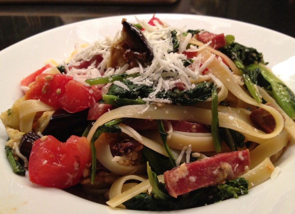 Fettuccine with garlic, eggplant, broccoli, tomatoes, sausage, and pecorino romano cheese on a white plate.