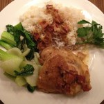 Sauteed chicken thighs with bacon, shallots and dry white wine, steamed Jasmine rice and sauteed baby bok choy with garlic on a white Wedgewood plate.