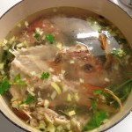 Fish broth cooking with red snapper, celery, leeks and parsley.