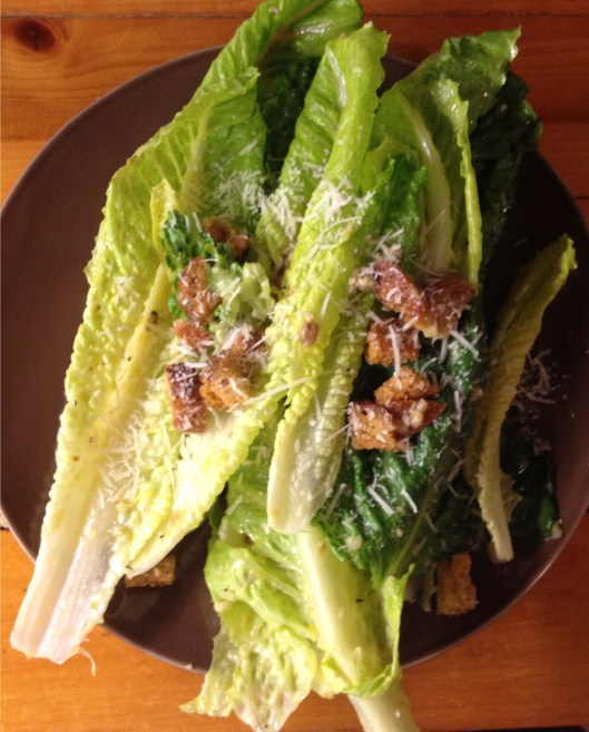Caesar salad topped with croutons and grated cheese on a brown plate.