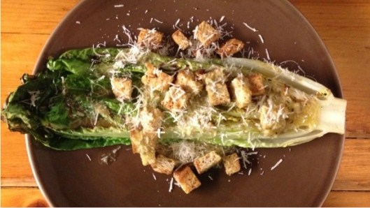 Caesar salad made with grilled Romaine lettuce, topped with croutons and grated cheese on a brown plate.